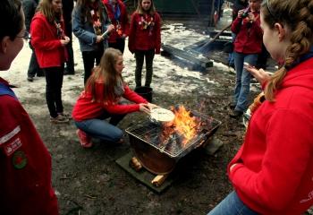 Explorers bakken taart op kampvuur Scouting St. George